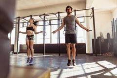 Athletes training hard at the gym. Muscular men and women exercising using skipping rope in gym. Couple workout with jumping ropes in cross training gym Stock Image