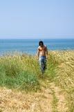 Muscular model walking in a corn field. Muscular male model on the beach walking in a corn field Stock Photo