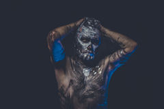 Muscular naked man covered with paint and mud skin Stock Image