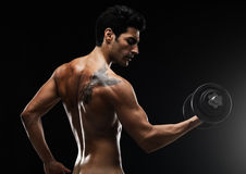 Muscular naked man lifting dumbbell Royalty Free Stock Photography