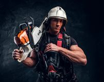 Portrait of muscular man with chainsaw and respirator. Muscular pensive man in helmet is looking away. He put his chainsaw on shoulder. With another hand he stock photography