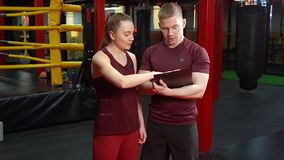 Muscular personal coach writing on clipboard and discussing the training plan to young woman in cross training gym