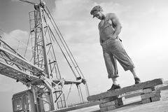 Muscular retro handyman standing on top of the building under co Royalty Free Stock Photo