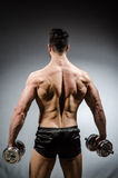 Muscular ripped bodybuilder with dumbbells Stock Images