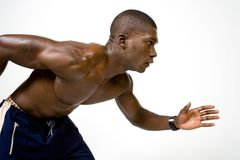 Muscular runner. Muscular African American athlete in running position Stock Photos