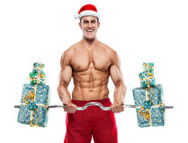 Muscular Santa Claus doing exercises with gifts over white backg Stock Photography