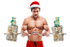 Muscular Santa Claus doing exercises with gifts over white backg Royalty Free Stock Photo