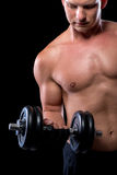 Muscular sexy guy picks up a   dumbbell Stock Photo