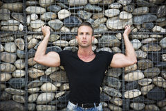 Muscular sexy man in front of stone wall, Stock Image