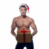 Muscular, sexy santa claus with gift Stock Images