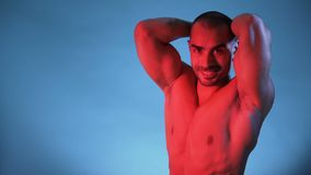 Muscular And Sexy Torso Of Young Man, Bodybuilder Isolated on Blue Background. Male Fitness Model Flexing muscles, isolated on blue background. Studio shot stock video footage