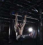Muscular shirtless athlete doing exercises on horizontal bar in Stock Photos