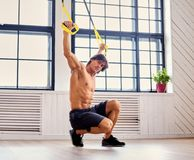 A man doing workouts with suspension trx straps. Muscular shirtless gymnast male doing workouts with suspension trx straps in a room Royalty Free Stock Photography