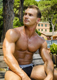 Muscular Shirtless Hunk Man Outdoor in City Park. Muscular Handsome Shirtless Hunk Man Outdoor in City Park. Showing Healthy Muscle Body Royalty Free Stock Photos