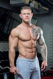 Muscular shirtless man with blue eyes and tattoo poses with EZ curl bar in a gray pants in a gym royalty free stock image