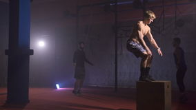 Muscular shirtless man doing twisting backflip jump off the box at the gym in slow motion. Crossfit jumps and flip exercises. Two men having a jump-rope stock video