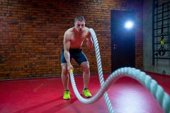 Muscular Shirtless Man in a Gym Exercises with Battle Ropes During His Fitness Workout High-Intensity Interval Training. Muscular Shirtless Man in a Gym Royalty Free Stock Photography