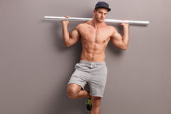 Muscular shirtless man holding a metal pipe. Muscular shirtless man carrying a gray metal pipe on his shoulders and leaning against a gray wall Royalty Free Stock Photos