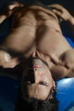 Muscular shirtless man laying down, belly up Stock Image