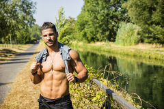 Muscular shirtless man outdoor by small river Stock Photos