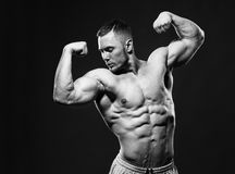 Muscular shirtless man in studio over dark background shows his muscles. royalty free stock image