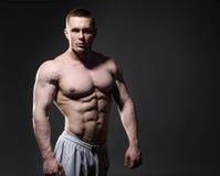 Muscular shirtless man in studio over dark stock photo