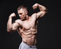 Muscular shirtless man in studio over dark royalty free stock image