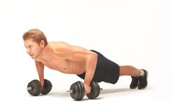 Muscular shirtless sportsman doing push-ups with dumbbells on white background. Young muscular sportsman making push-ups with bent arms on black dumbbells Royalty Free Stock Photos