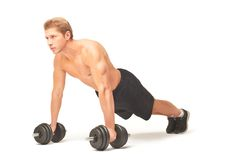 Muscular shirtless sportsman doing push-ups with dumbbells on white background. Young muscular sportsman making push-ups with straight arms on black dumbbells Royalty Free Stock Photography