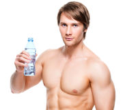 Muscular shirtless sportsman holds water. Royalty Free Stock Photo