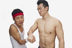 Muscular shirtless young man beating another young man at arm wrestling, studio shot Royalty Free Stock Photos