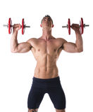 Muscular shirtless young man exercising shoulders with dumbbells Stock Photography