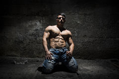 Muscular shirtless young man on his knees with light above head. In grunge, vintage place Stock Photography