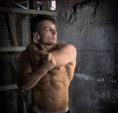 Muscular shirtless young man inside abandoned building Royalty Free Stock Photos