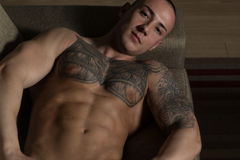 Muscular Shirtless Young Man Laying in Bed Royalty Free Stock Images
