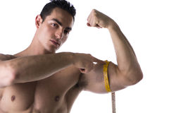 Muscular shirtless young man measuring arm with tape measure Royalty Free Stock Image
