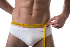Muscular shirtless young man measuring waist with tape measure. Close-up of hips and abdomen area Stock Photo
