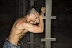 Muscular shirtless young man resting against metal column Stock Photography