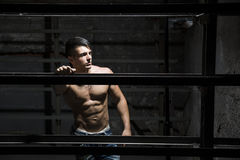 Muscular shirtless young man resting against metal structure Stock Image