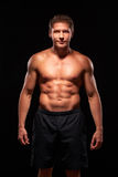 Muscular smiling powerful shirtless man on black background Stock Image