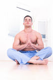 Muscular spiritual man doing yoga. Muscular spiritual half naked man in blue pajamas doing yoga indoor stock photos