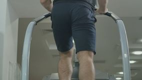 Young muscular man train legs in the gym on the staircase. Muscular sportive man has a sport exercises in the gym. Handsome guy is moving up stairs and looks stock footage