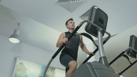 Young man training the legs moving up stairs in the gym. Muscular sportive man has a sport exercises in the gym. Handsome guy is moving up stairs and looks stock footage