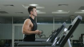 Muscular guy running on the treadmill stock video footage