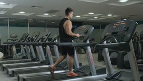 Muscular guy walks on treadmill in the gym. Muscular sportive man has a sport exercises in the gym. Handsome guy walks on the running track and looks forward stock video footage