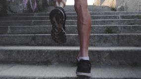 Muscular sportive tanned male legs run up stairs. Close up back view of strong powerful male legs. Slim active man runs up stairs.