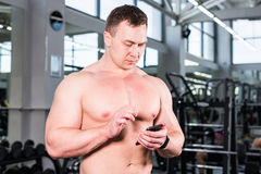 Muscular sports man use activity tracker. In gym Royalty Free Stock Image
