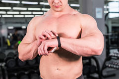 Muscular sports man use activity tracker. In gym Stock Image