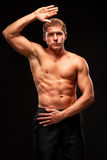 Muscular sportsman on black background demonstrating biceps, triceps, pectoral muscles Royalty Free Stock Photography