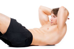 Muscular sportsman do exercise on a floor. Royalty Free Stock Images